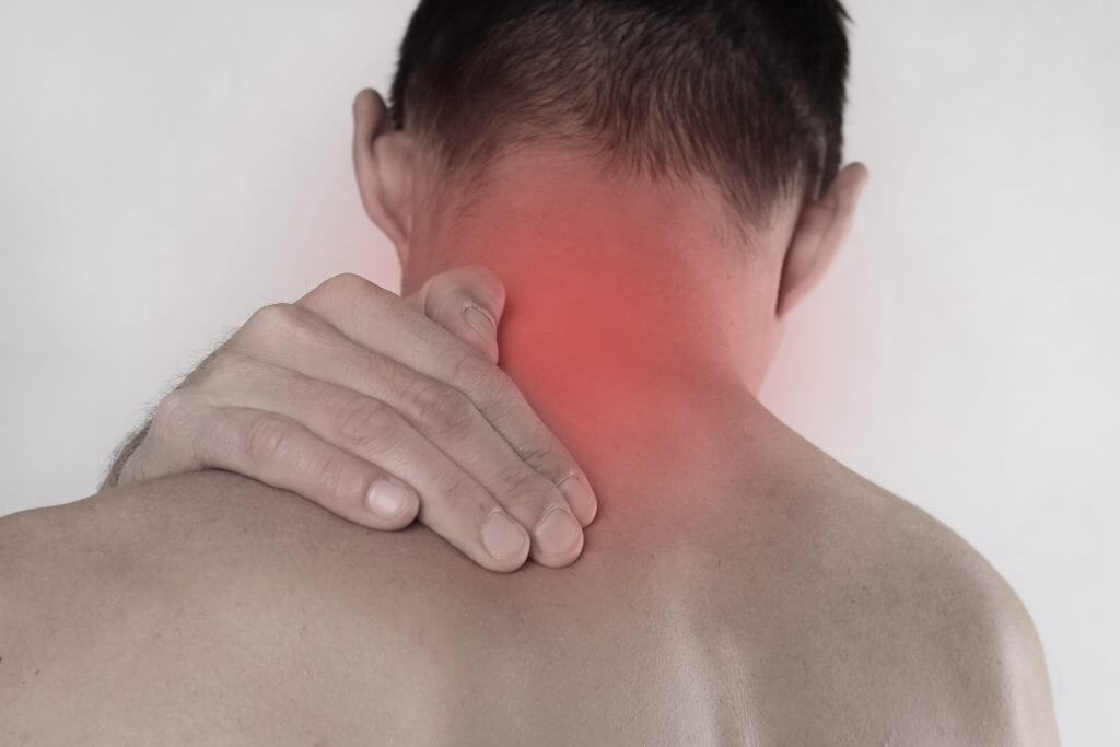 Close up of man rubbing his painful neck. Pain relief concept